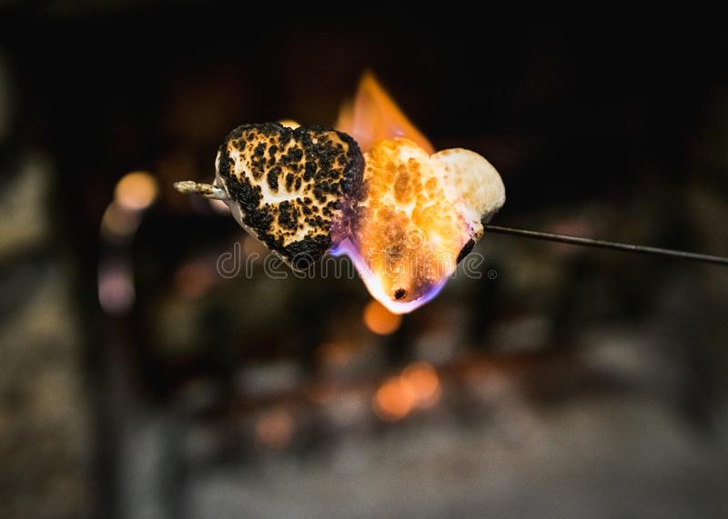 Flaming and Blackened, Two Heart Shaped Marshmallows royalty free stock photo