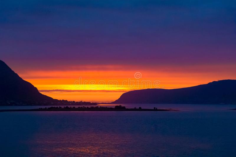 Colorful midsummer sky in orange, yellow and violet at Norwegian Sea, North Norway, Flaming sunset. Blazing sky in Norway at the end of June at midsummer time royalty free stock photography