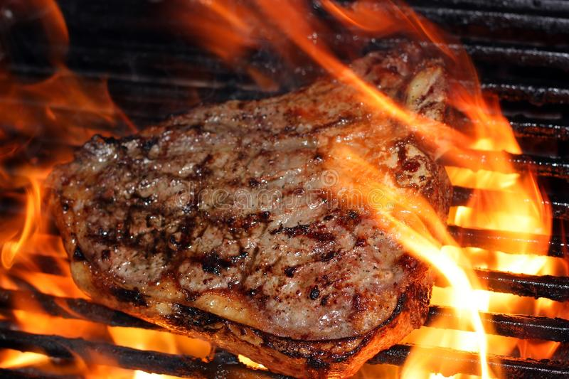 Flaming Steak. A cooking t-bone steak on an open barbeque grill stock photos