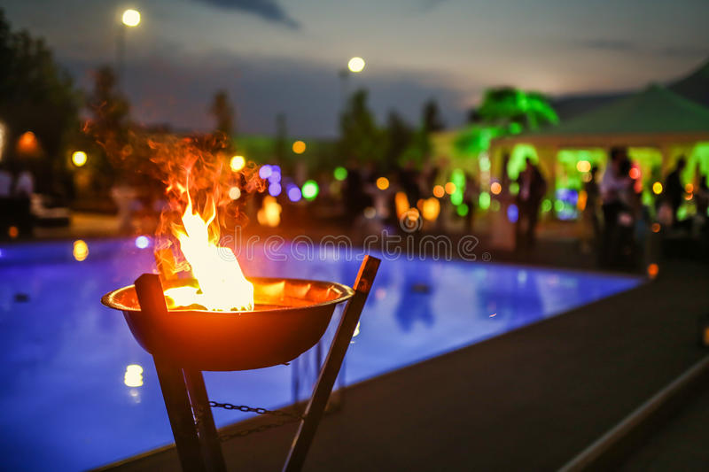 Flaming torch at sunset by the pool royalty free stock images