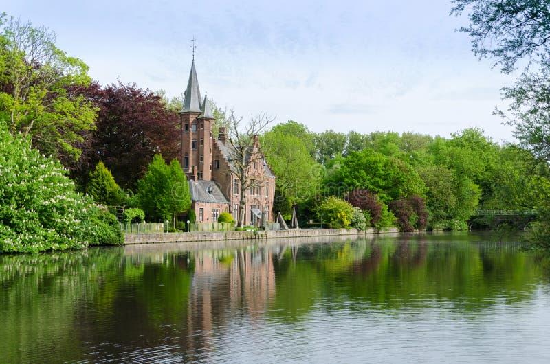 Flamländsk stilbyggnad som reflekterar i Minnewater sjön fotografering för bildbyråer