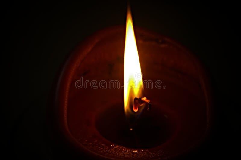 Flamma av en stearinljus i mörkret arkivfoton