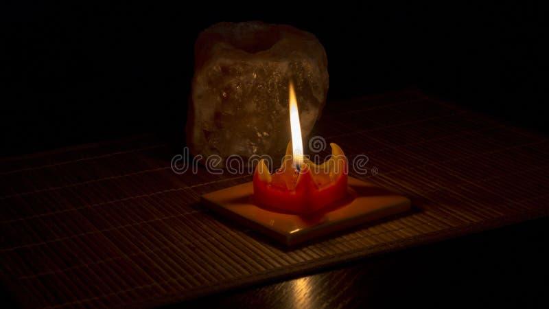 Flamman av den röda stearinljuset exponerar stenen saltar royaltyfria foton