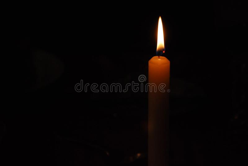 Flamman av ett stearinljusljus i mörker royaltyfria foton