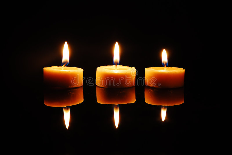 flammande stearinljus tre wax arkivbild