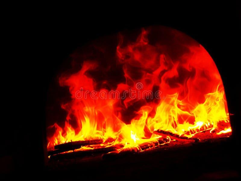 Flamme dans le four foncé image stock