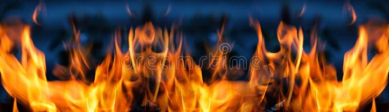 Flamme orange lumineuse sur un fond bleu photo stock
