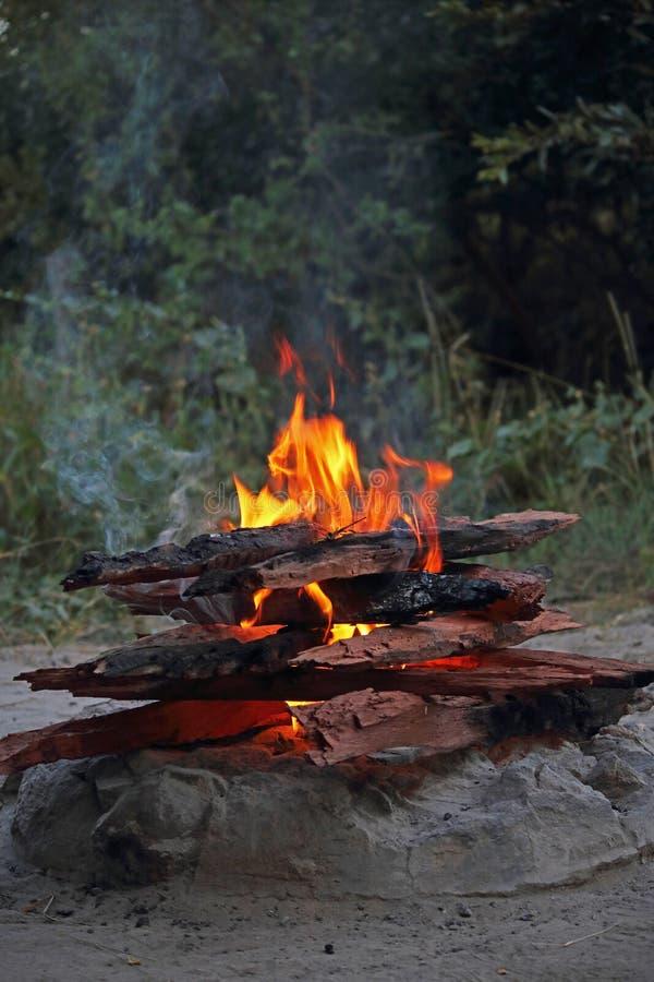 FLAMMEN UND RAUCH, DIE WEG EIN LAGERFEUER AN DER DÄMMERUNG KOMMEN stockbilder