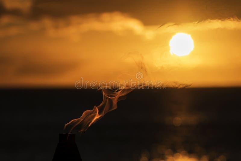 Flammen von einer Fackel kreuzen den Sun bei Sonnenuntergang stockfoto