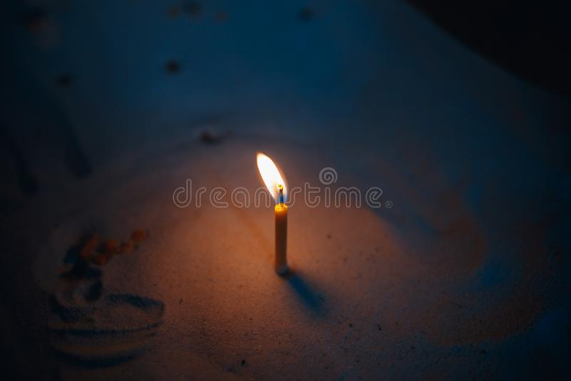 Flammen von votive Kerzen auf dem Sand stockfoto