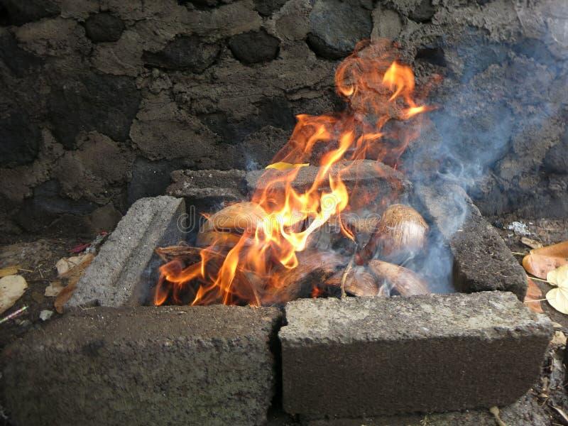 Flammes de brûler les cosses sèches de noix de coco images stock
