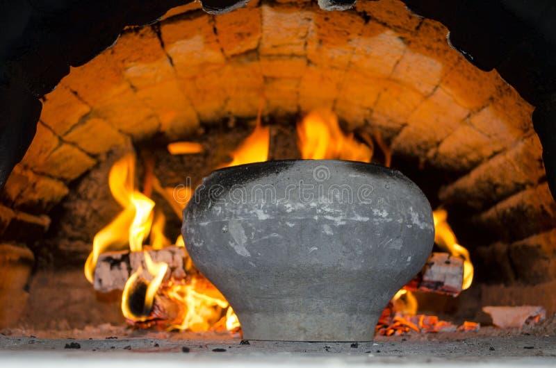 Flammes du feu et du pot dans le four mis le feu en bois dans la maison de village images stock