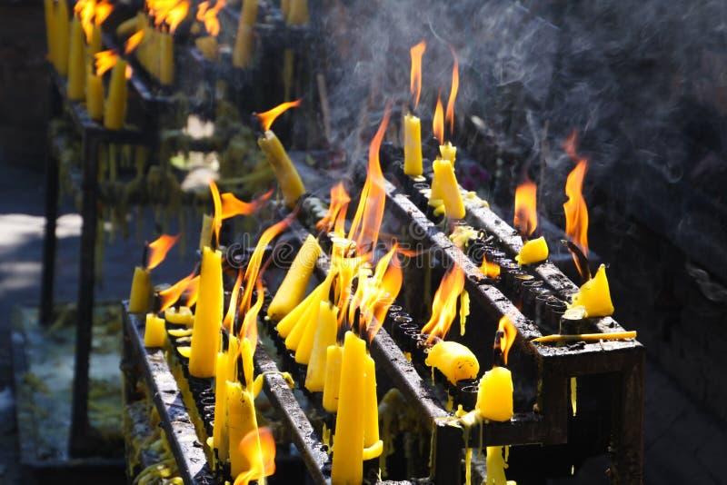 Flammor och rök av gula brinnande stearinljus i den buddistiska templet, Chiang Mai, Thailand arkivbilder
