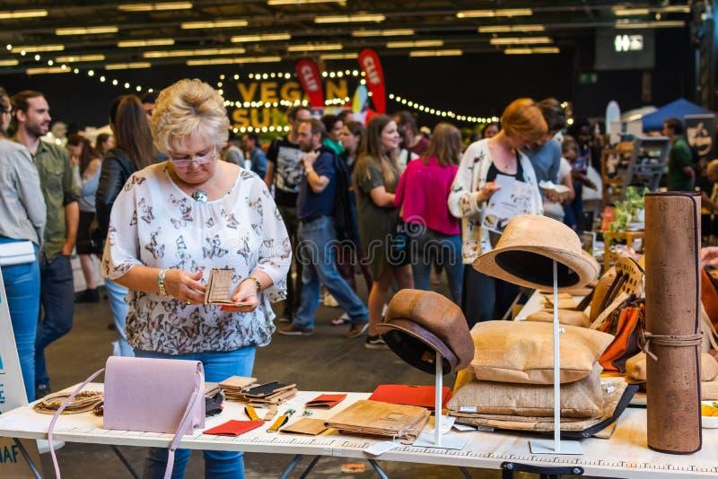 Flanders Expo, Gent Ghent, Belgio, 17 agosto 2019: Festa estiva vegetariana, donna che controlla cappelli vegani, borsetta immagine stock