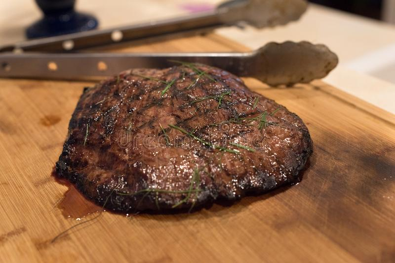 Flank Steak fresh off the grill. Juicy Grilled Flank steak, fresh off the grill on bamboo cutting board stock photo