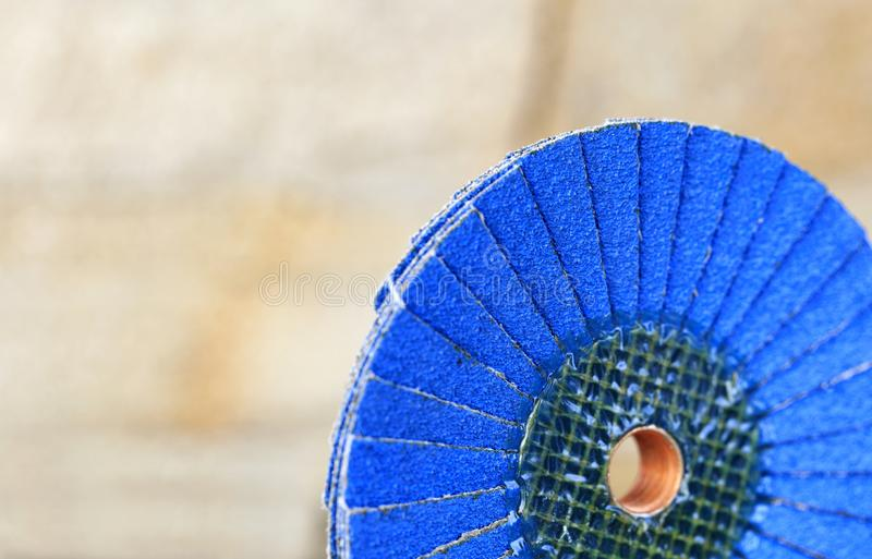 Flap grinding wheel blue on wood and metal on a light beige background in unsharp royalty free stock images