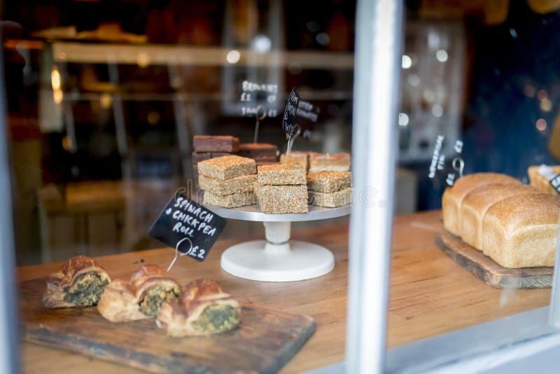 Flapjack en cake de selectie op een vertoning op een cake bevindt zich in een venster van de bakkerijwinkel stock fotografie