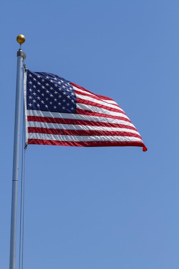 Flapping da bandeira americana no vento em um dia claro imagem de stock