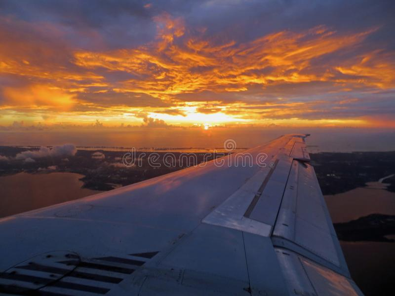 Sunset landing view over airplane wing. Flaps on the wing are down for landing as I am transfixed by a stunning, vibrant sunset in golds, purples and blues seen royalty free stock image