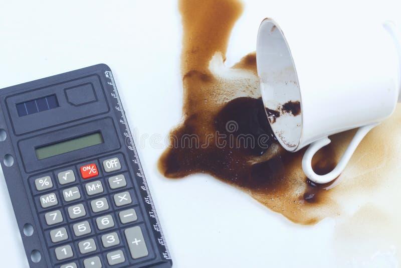 Flaque de café, cuvette de café et une calculatrice. photographie stock