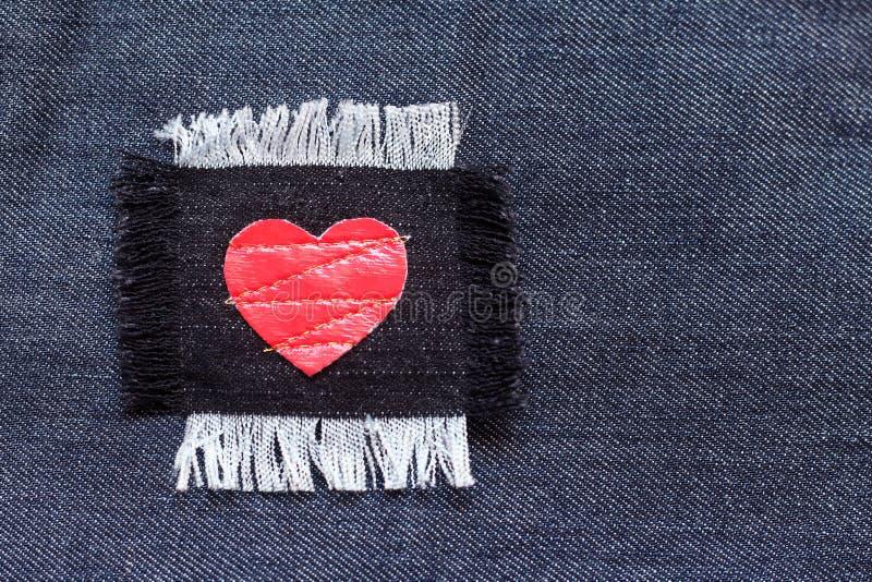 Flard met rood hart op de jeansstof royalty-vrije stock afbeelding