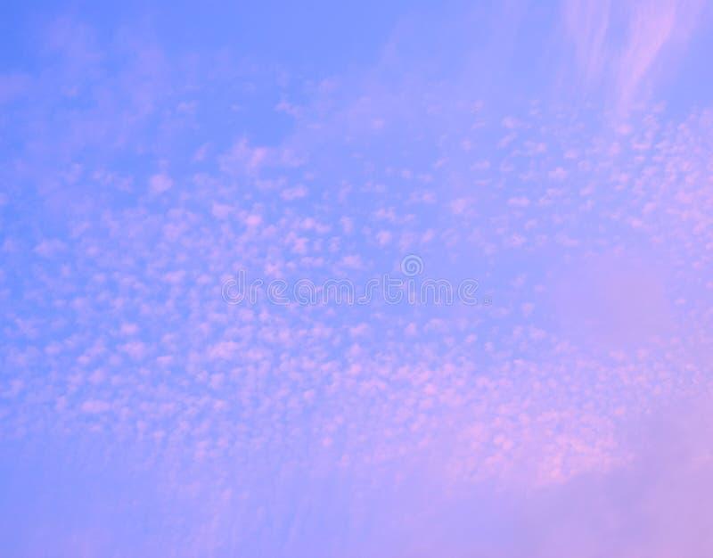 Flarden van Wolken in Blauwe Hemel met tinten van Roze - Natuurlijke Abstracte achtergrond stock foto