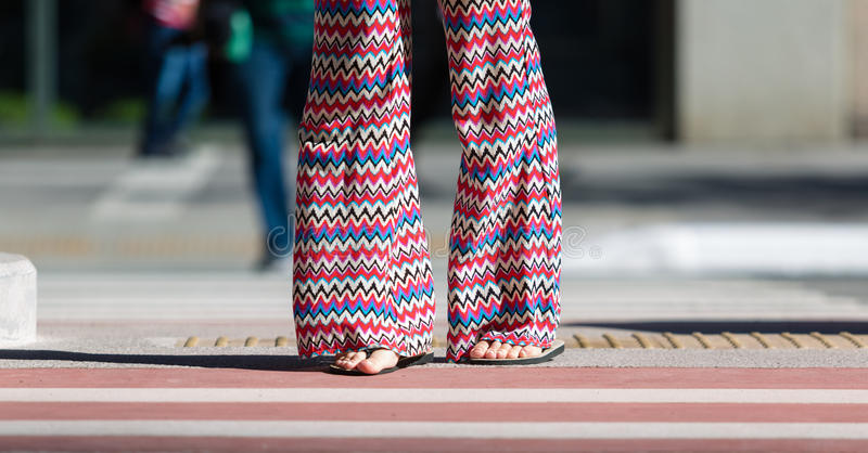 Flare Pants. Brazilian girl crossing the street with rubber sandals and flare pants stock image