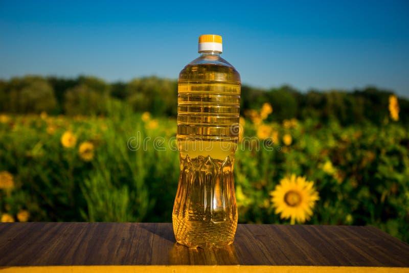 Flasche Öl auf hölzernem Stand mit Sonnenblumenfeldhintergrund Sonnenblumenöl verbessert Hautgesundheit stockfotografie