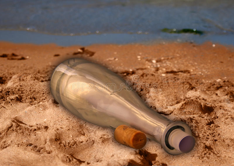 Flasche auf dem Sand mit einer Meldung stockfotografie