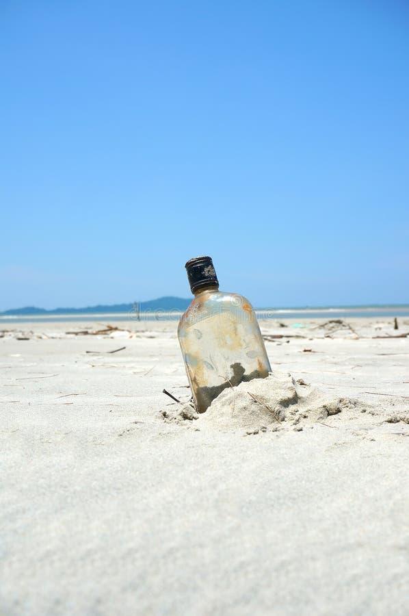 Flasche auf einem Sandstrand lizenzfreies stockfoto