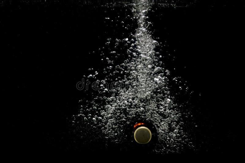 Flasche Bier unter Wasser mit Luftblasen Getrennt auf schwarzem Hintergrund lizenzfreies stockbild