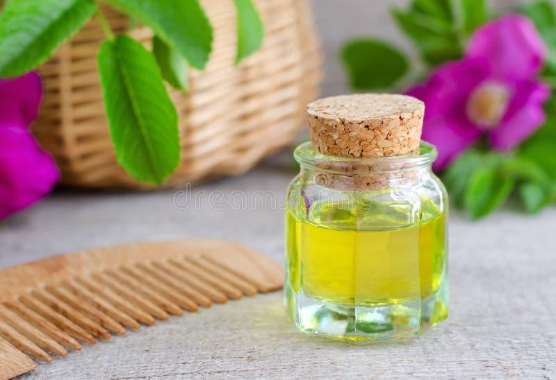 Flasche des natürlichen kosmetischen (Massage) Öls und des hölzernen Haarkammes lizenzfreie stockbilder