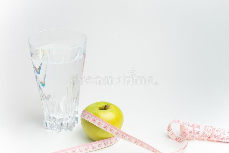 Flasche des Wassers, des Apfels und des messenden Bands lokalisiert auf weißem Hintergrund lizenzfreie stockfotos