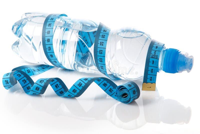 Flasche des Wassers und des Maßbands lizenzfreie stockfotos