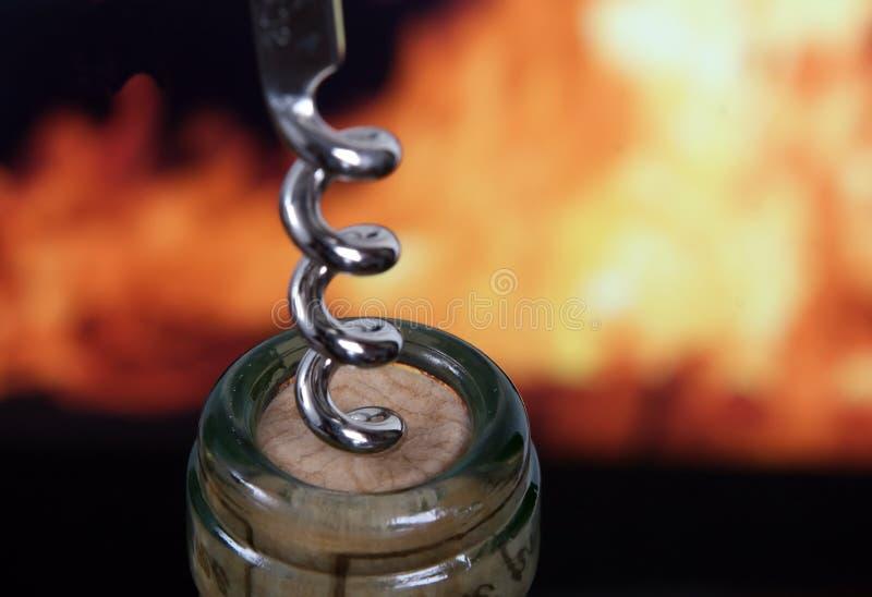 Flasche des weißen Weins durch rotes Feuer mit Korkenzieher stockfotos