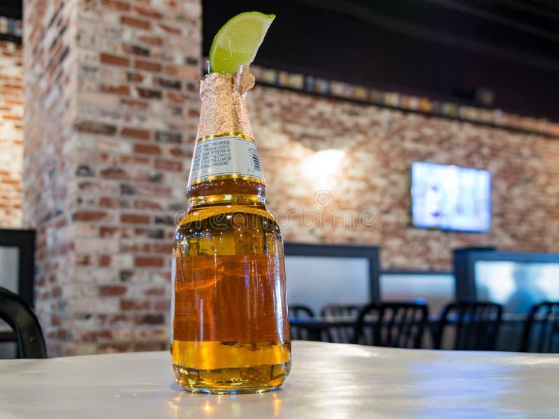Flasche eines kalten Bieres mit einer Stückzitrone lizenzfreies stockbild