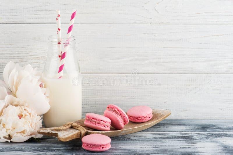 Flasche Milch mit rosa französischen Makronen stockfotografie