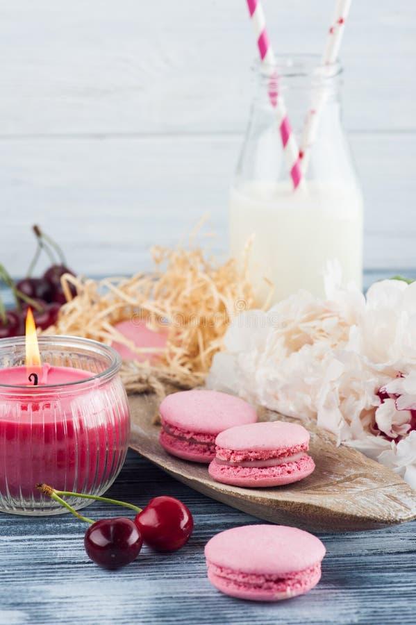 Flasche Milch mit rosa französischen Makronen lizenzfreie stockbilder