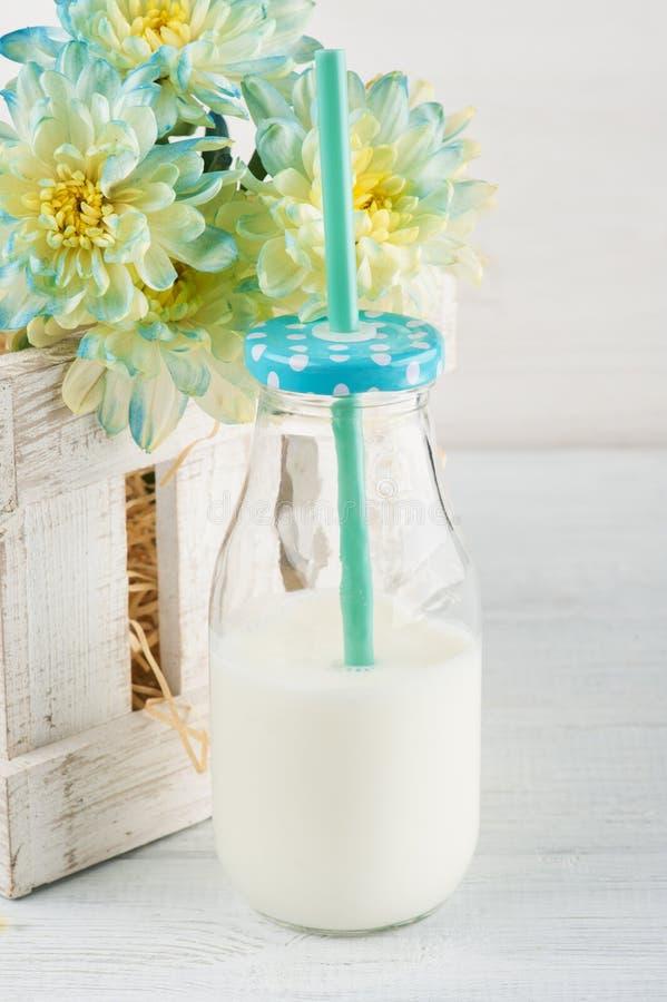 Flasche Milch mit Stroh und blauem Gänseblümchen stockbilder