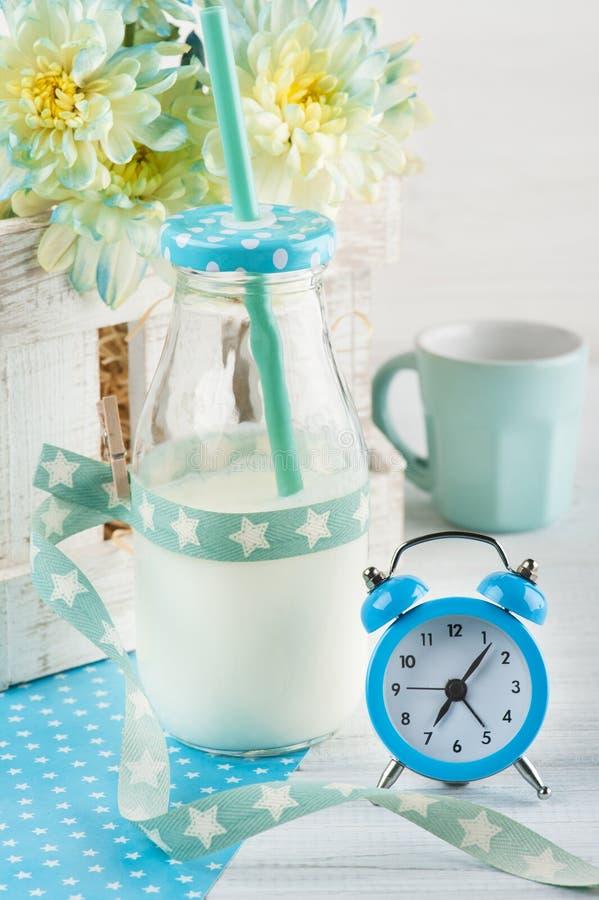 Flasche Milch mit Stroh und blauem Wecker lizenzfreies stockfoto