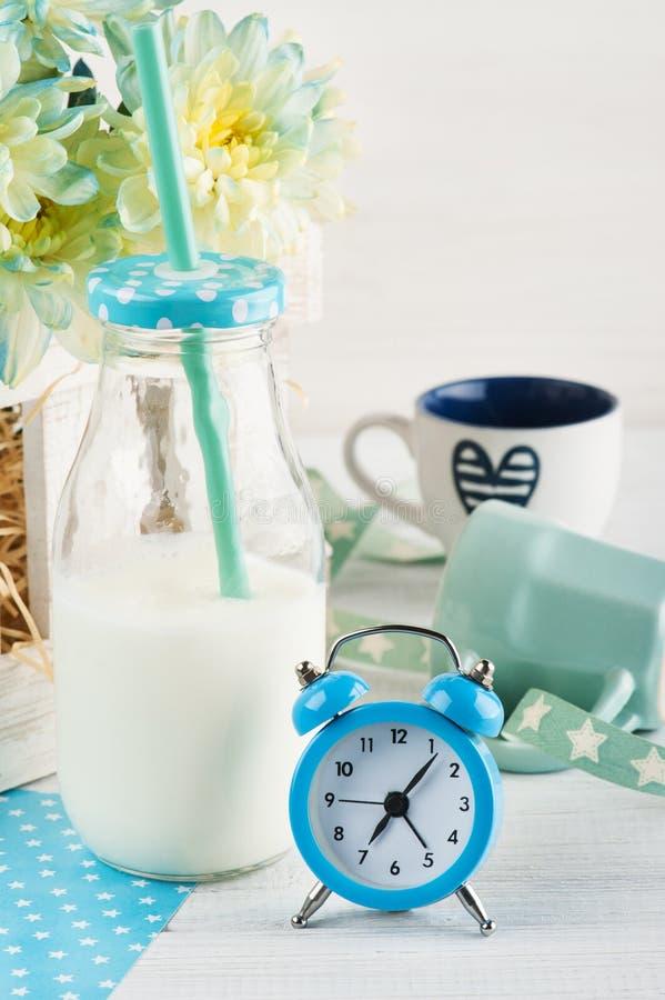 Flasche Milch mit Stroh und blauem Wecker stockfotos