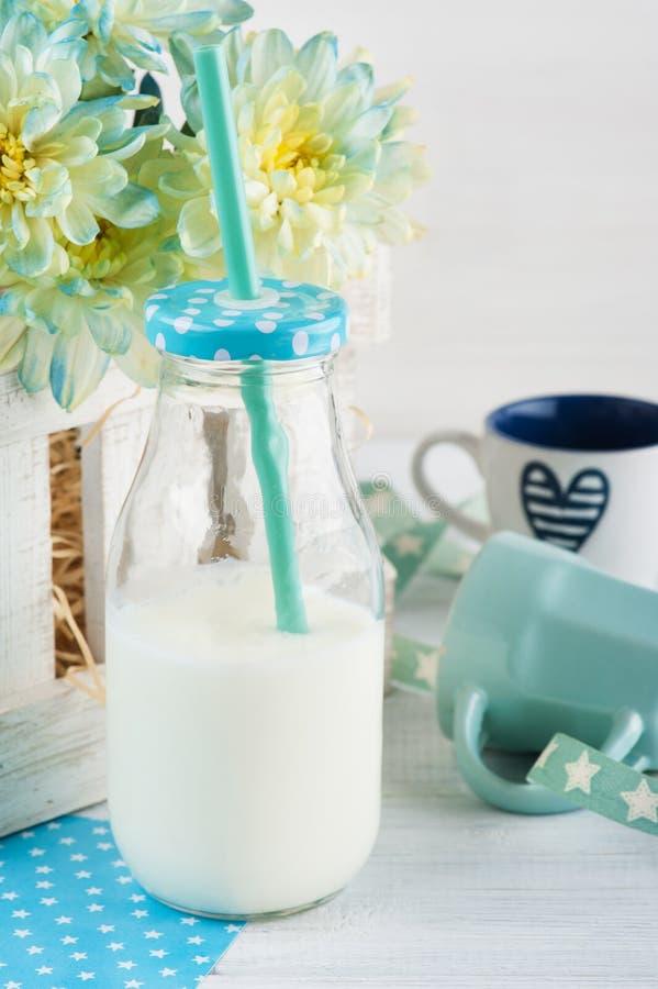 Flasche Milch mit Stroh und blauer Schale stockbild