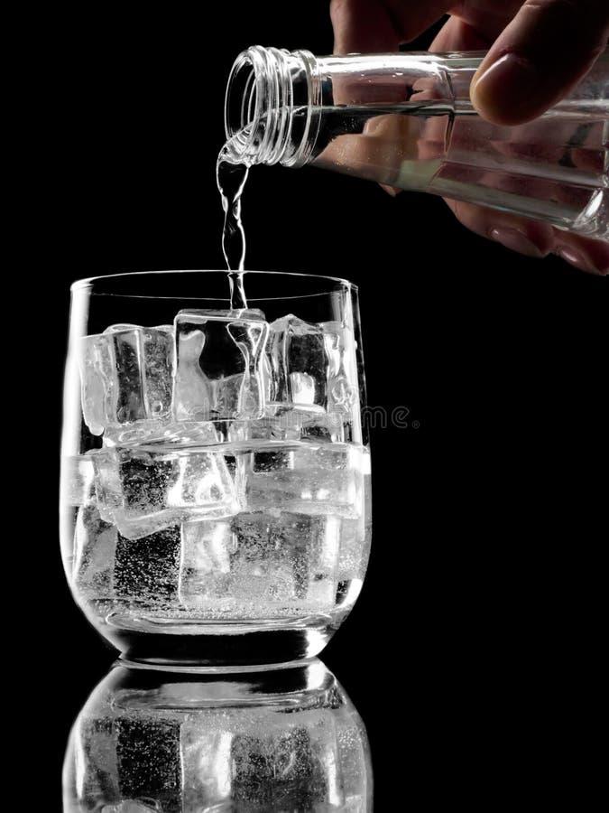 Flasche Mineralwasser des Sodas, das in Glas gießt lizenzfreie stockfotos