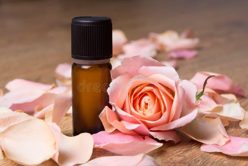 Flasche mit ätherischem Öl und den rosafarbenen Blumenblättern stockfotografie