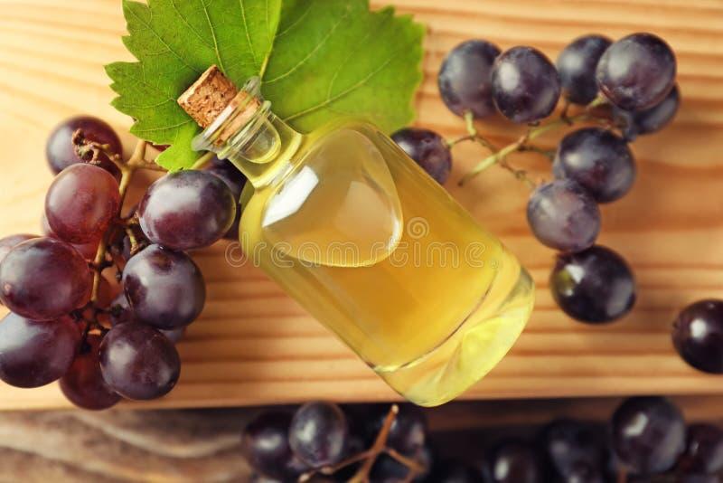 Flasche mit Öl und frischen Trauben auf hölzernem Brett, Draufsicht stockfoto