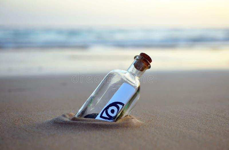 Flasche mit Augenikone am Strand, Nachmittag stockfotos