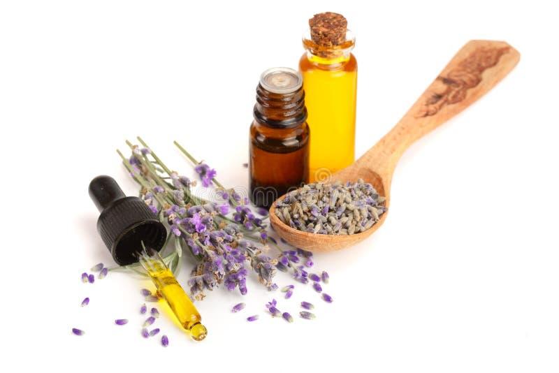 Flasche mit den Aromaöl- und -lavendelblumen lokalisiert auf weißem Hintergrund stockbild