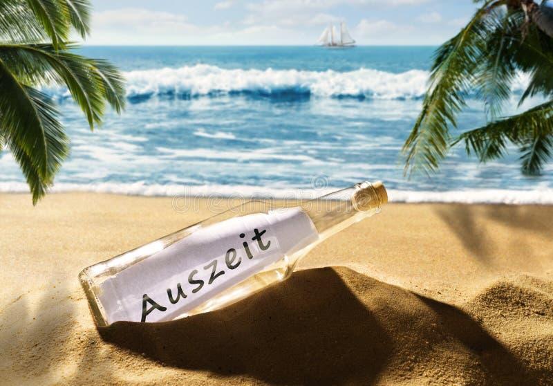 Flasche mit der Mitteilungszeit heraus auf dem Strand stockbild
