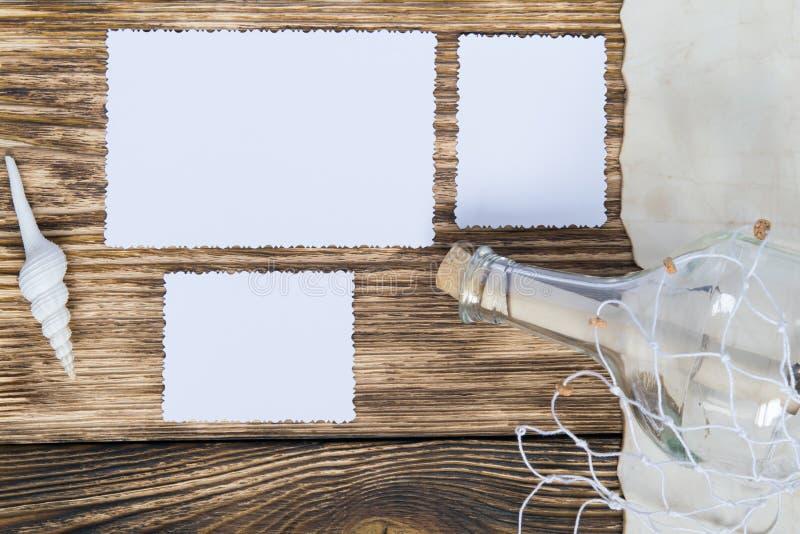 Flasche mit einer Mitteilung im Gitter auf dem Tisch und in drei leeren Fotos lizenzfreies stockfoto