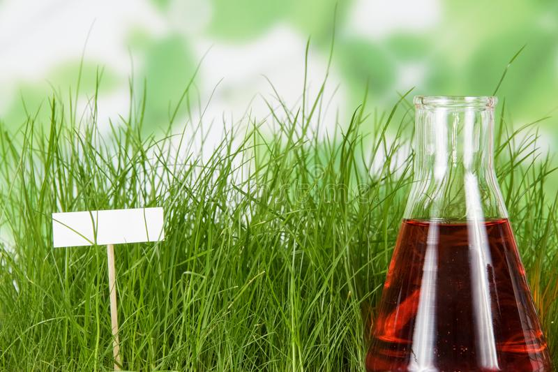 Flasche mit Flüssigdünger auf Hintergrund des grünen Grases und der leeren Karte stockfotos